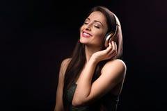 Mujer joven de goce hermosa que escucha la música en la radio h Fotos de archivo libres de regalías