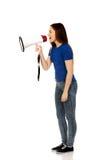 Mujer joven de griterío con el megáfono Imagenes de archivo