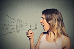 Mujer joven de griterío enojada que sostiene el megáfono Foto de archivo libre de regalías