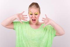 Mujer joven de griterío hermosa con maquillaje verde Fotografía de archivo libre de regalías