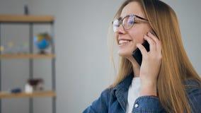 Mujer joven de Handosme usando el teléfono elegante en la agencia de viajes metrajes