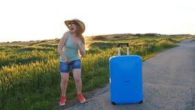 Mujer joven de Hapy con la maleta concepto del recorrido almacen de video