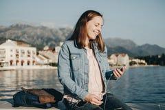 Mujer joven de Joyfull que escucha la música en los auriculares con el teléfono Imagen de archivo libre de regalías
