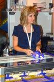 Mujer joven de JUNWEX Moscú 2014 que muestra a compradores la cadena del oro Imagen de archivo