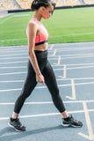 Mujer joven de la aptitud en la ropa de deportes que se coloca y que mira abajo en estadio corriente de la pista Fotos de archivo libres de regalías