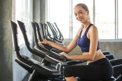 mujer joven de la aptitud en ropa de deportes que ejercita con biking en club del gimnasio del deporte entrenamiento de la muchac fotos de archivo