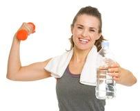 Mujer joven de la aptitud feliz que lleva a cabo pesas de gimnasia Fotos de archivo libres de regalías