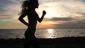 Mujer joven de la aptitud que activa en la playa en la puesta del sol metrajes