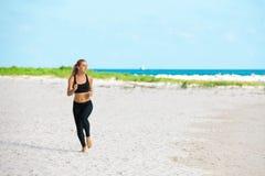 Mujer joven de la aptitud que corre en la playa Foto de archivo