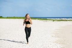 Mujer joven de la aptitud que corre en la playa Imagen de archivo