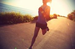 Mujer joven de la aptitud que corre en rastro de la playa de la salida del sol imagenes de archivo