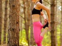 Mujer joven de la aptitud que estira sus piernas en el pino Forest Female Runner Doing Stretches Concepto sano de la forma de vid foto de archivo libre de regalías