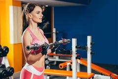 Mujer joven de la aptitud que hace ejercicio con el barbell en el gimnasio Foto de archivo libre de regalías