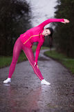Mujer joven de la aptitud que hace ejercicio en un día lluvioso Imagenes de archivo