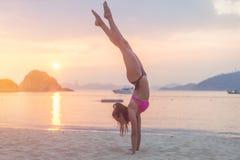 Mujer joven de la aptitud que hace ejercicio de la posición del pino en la playa en la salida del sol Muchacha deportiva en costa foto de archivo