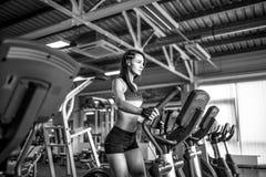 Mujer joven de la aptitud que hace ejercicios cardiios en el gimnasio que corre en una rueda de ardilla Imagen de archivo libre de regalías