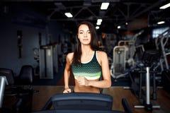 Mujer joven de la aptitud que hace ejercicios cardiios en el gimnasio que corre en una rueda de ardilla Foto de archivo