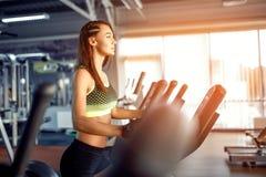 Mujer joven de la aptitud que hace ejercicios cardiios en el gimnasio que corre en una rueda de ardilla Foto de archivo libre de regalías