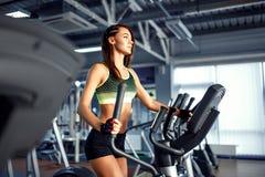 Mujer joven de la aptitud que hace ejercicios cardiios en el gimnasio que corre en una rueda de ardilla Fotografía de archivo libre de regalías