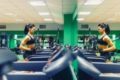 Mujer joven de la aptitud que hace ejercicios cardiios en el gimnasio que corre en un entrenamiento femenino del corredor de la r Fotos de archivo