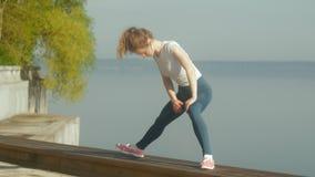 Mujer joven de la aptitud que hace ejercicios en el gimnasio en un al aire libre en la orilla del río almacen de video