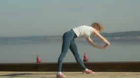 Mujer joven de la aptitud que hace ejercicios en el gimnasio en un al aire libre en la orilla del río almacen de metraje de vídeo