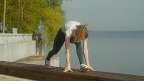 Mujer joven de la aptitud que hace ejercicios en el gimnasio en un al aire libre en la orilla del río metrajes