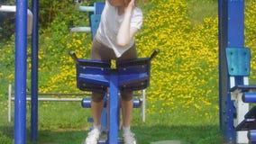 Mujer joven de la aptitud que hace ejercicios en el gimnasio en un parque al aire libre almacen de metraje de vídeo