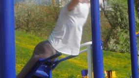 Mujer joven de la aptitud que hace ejercicios en el gimnasio en un parque al aire libre almacen de video