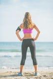 Mujer joven de la aptitud que se coloca en la playa. vista posterior Fotos de archivo