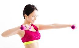 Mujer joven de la aptitud que se resuelve con pesas de gimnasia Imagenes de archivo