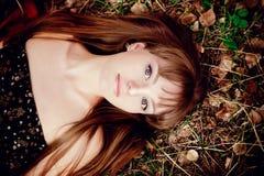 Mujer joven de la belleza con el pelo rojo en campo de oro en la puesta del sol Imágenes de archivo libres de regalías