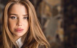 Mujer joven de la belleza contra interior de la casa Imágenes de archivo libres de regalías
