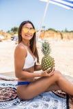 Mujer joven de la belleza en bañador de la piña y sombrero del sol en la playa Vocación del verano imagen de archivo libre de regalías