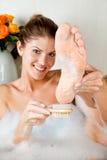 Mujer joven de la belleza en el baño que se lava el pie Fotografía de archivo libre de regalías