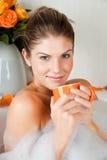 Mujer joven de la belleza en el baño que bebe té herbario Fotos de archivo