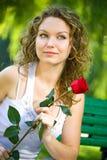 Mujer joven de la belleza en parque con la flor Imagen de archivo