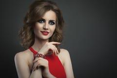 Mujer joven de la belleza en tiro rojo del estudio del retrato de la moda Foto de archivo libre de regalías