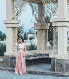 Mujer joven de la belleza en un vestido rosa claro Fotografía de archivo