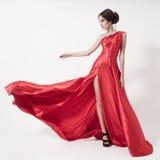Mujer joven de la belleza en vestido rojo que agita. Fondo blanco. Imagen de archivo