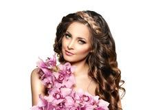 Mujer joven de la belleza, pelo rizado largo de lujo con la flor de la orquídea H Fotos de archivo libres de regalías