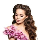 Mujer joven de la belleza, pelo rizado largo de lujo con la flor de la orquídea H Foto de archivo libre de regalías
