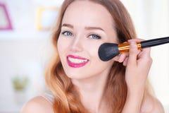 Mujer joven de la belleza que aplica maquillaje Foto de archivo libre de regalías