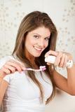 Mujer joven de la belleza que aplica sus dientes con brocha Fotografía de archivo libre de regalías