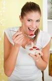 Mujer joven de la belleza que come la pulpa con la fresa Imagenes de archivo