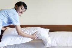 Mujer joven de la criada que prepara el dormitorio Imagen de archivo