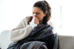 Mujer joven de la enfermedad que estornuda en un tejido Imagen de archivo