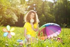 Mujer joven de la felicidad en una comida campestre en el parque Fotos de archivo