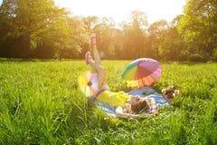Mujer joven de la felicidad en una comida campestre en el parque Foto de archivo libre de regalías