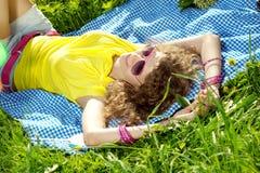Mujer joven de la felicidad en una comida campestre en el parque Imágenes de archivo libres de regalías